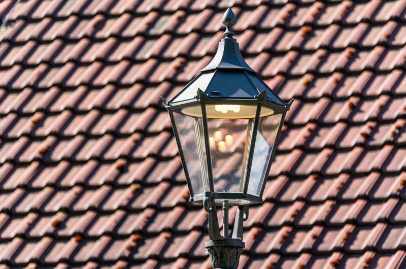 Low angle view of illuminated street light against building