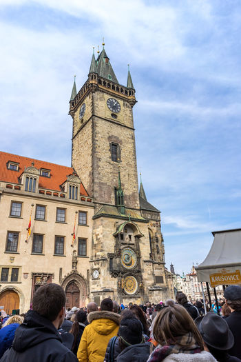 Rear view of tourists in front of astronomical clock tower