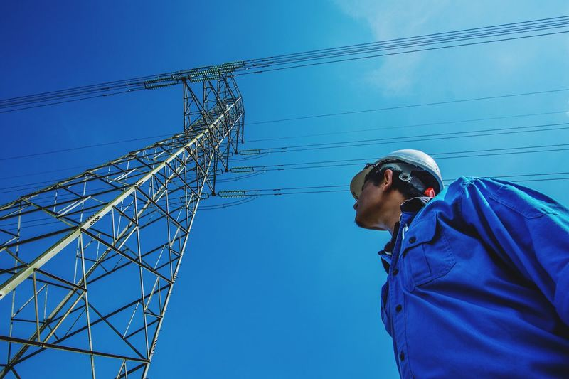 Power line staff with transmission tower Electricity  Young Adult Cable Young Men One Young Man Only Business Finance And Industry Protection Technology Low Angle View Fuel And Power Generation Hardhat  Occupation Electricity Pylon Men One Man Only Standing Headwear One Person Industry Blue Built Structure Customer  Bills Bills To Pay Powerline