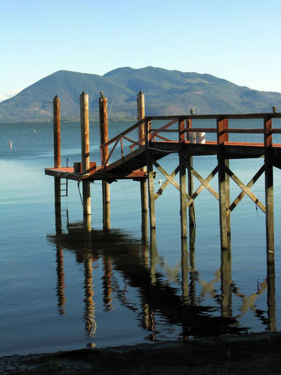 Perfect reflection of a wooden pier on the shore of Clearlake, Clear Lake, California Clear Sky Clearlake Clearlake, Ca. Dock Glassy Water Lake Lake Shore Mountain Nature No People Outdoors Piers Reflection Reflection In The Water Scenics Still Water Tranquil Scene Water Wooden Dock Wooden Pier