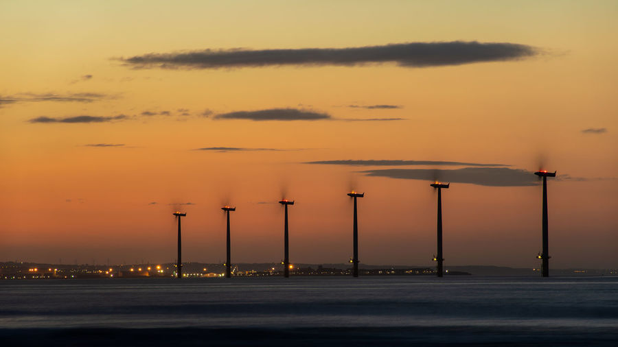 Windmills in sea against sky during sunset
