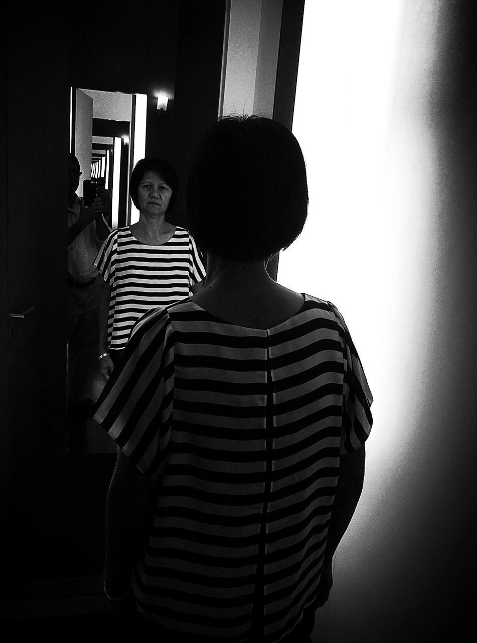 Rear View Of Senior Woman Looking In Mirror At Home