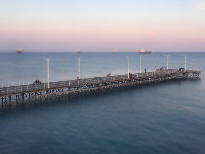 Pier on sea during sunset