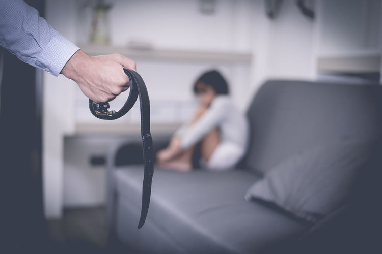 Cropped Hand Of Young Man Holding Belt While Scared Daughter Sitting On Sofa At Home##