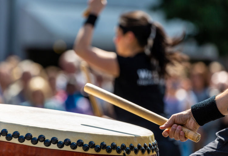 Midsection of artist playing drum against crowd