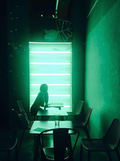 Man sitting on table in illuminated room