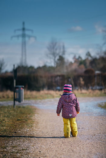 Rear view of girl in warm clothing standing on dirt road