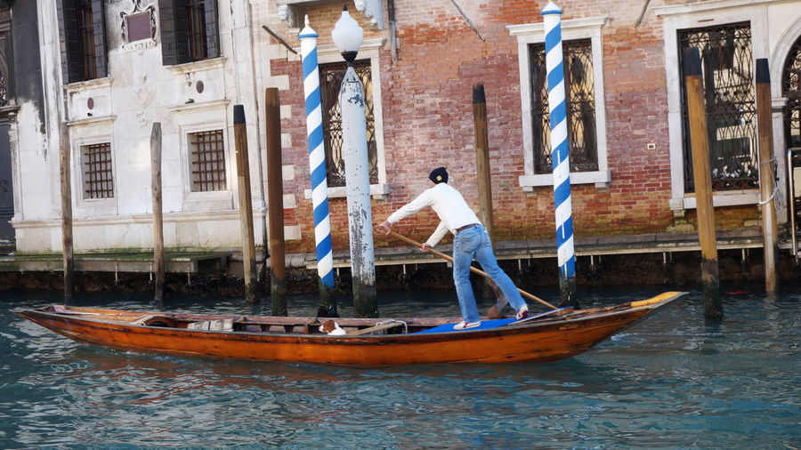 Full length of man boating on grand canal against building in city