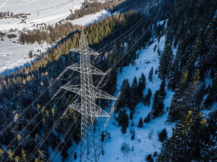 High angle view electrical pylon on snow covered land