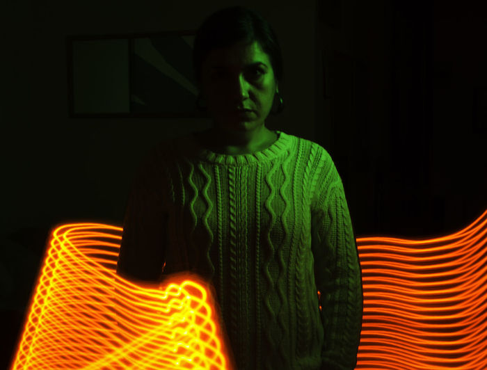 Adult Beautiful Woman Black Background Contrast Green Color Illuminated Light Trail Light Wand Long Exposure One Person One Woman Only Orange Color Portrait Standing Surreal Sweater Yongnuo YN360 Young Adult