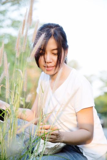 Smiling young woman looking at plants