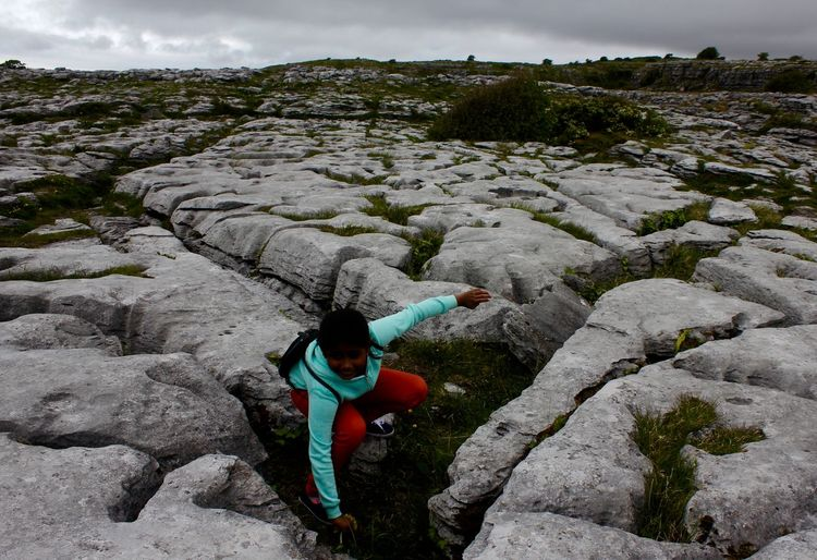 Boy crouching amidst rock formations at the burren