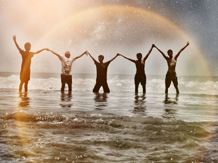 Male friends holding hands with arms raised while standing in sea against sky