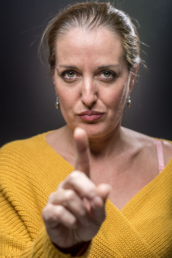 Portrait of woman pointing against black background