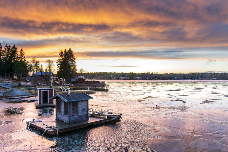 Floating Huts On Frozen Lake Against Sky During Sunset