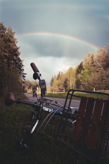 Rainbow in a cloudy sky with a bicycle lying on a sidewalk.