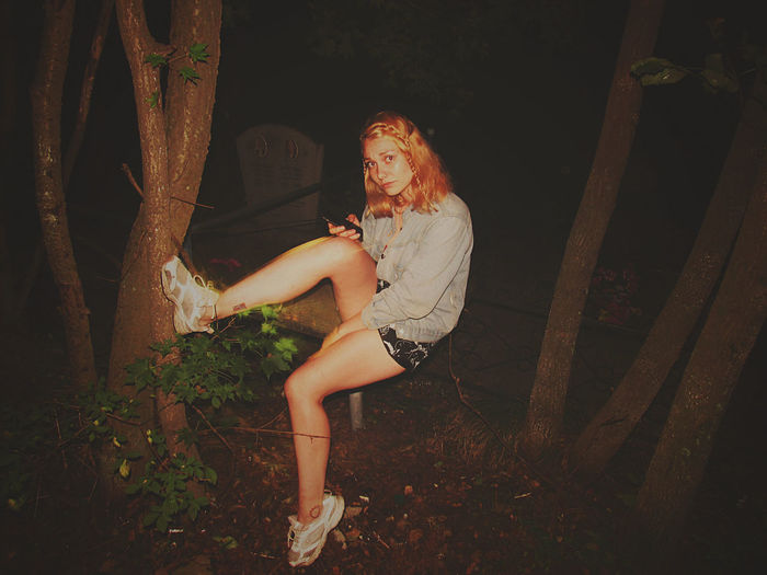 Portrait of woman sitting on railing at park during night