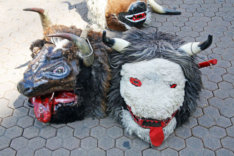 High angle view of demon masks on footpath