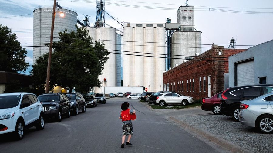Rear view of boy running on street against factory in city
