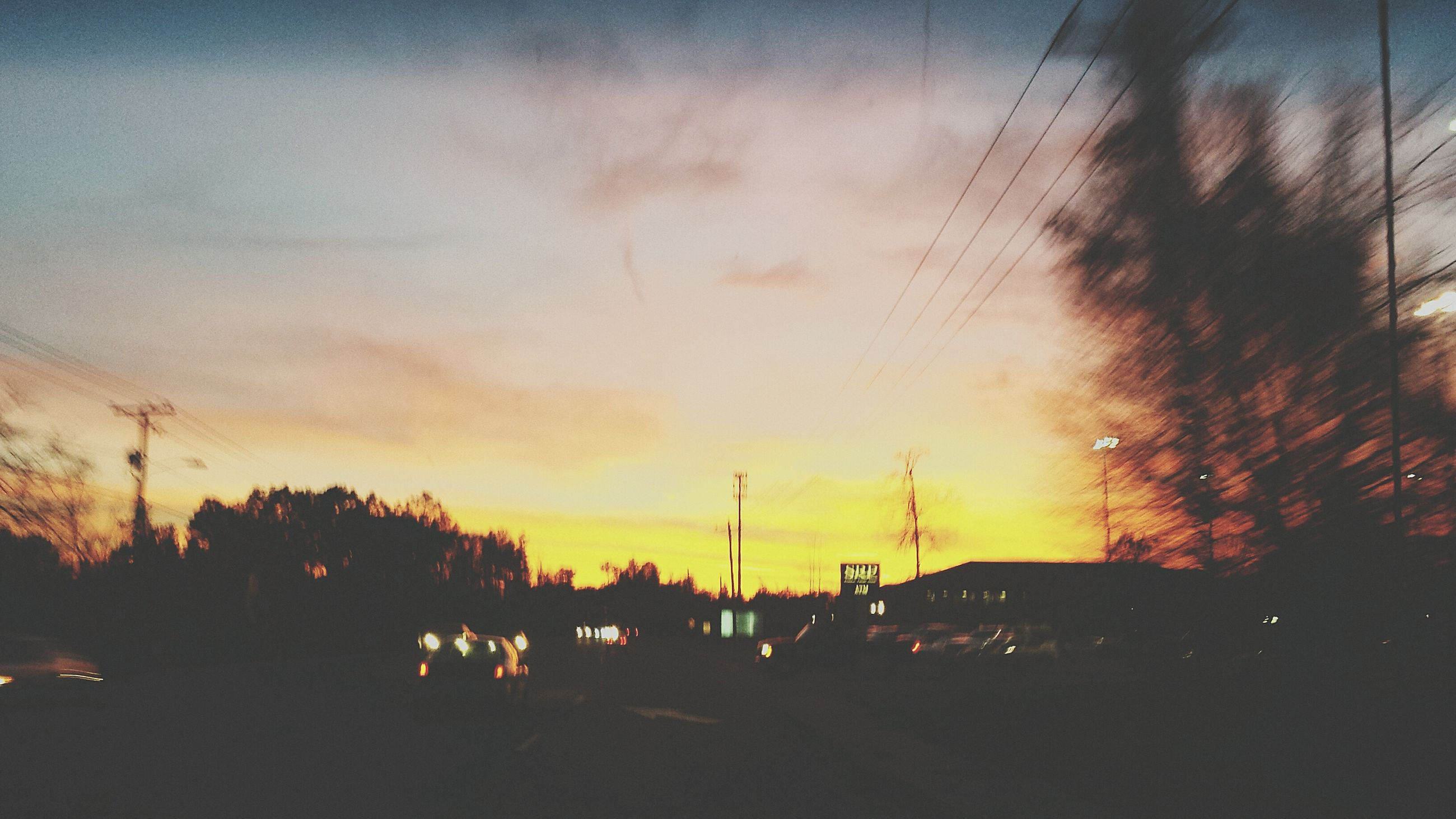 sunset, silhouette, sky, power line, electricity pylon, orange color, building exterior, cloud - sky, dusk, electricity, built structure, street light, city, power supply, tree, architecture, nature, outdoors, beauty in nature, connection