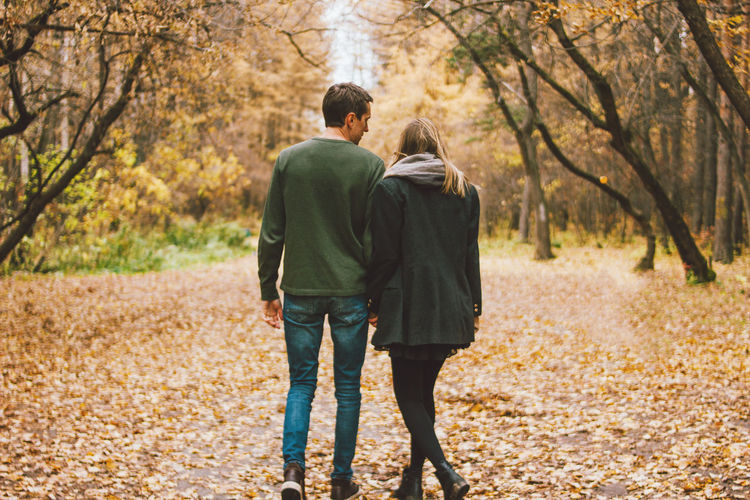 Rear view of couple walking in autumn forest