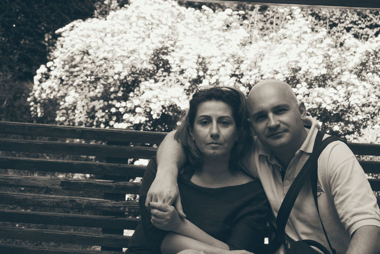 Portrait Of Couple Sitting On Bench At Park