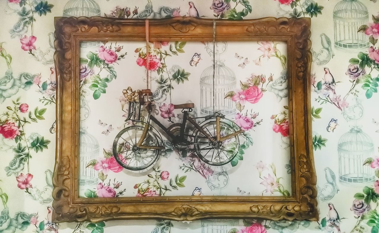 indoors, no people, representation, frame, human representation, art and craft, picture frame, floral pattern, mirror, design, creativity, craft, wall - building feature, pattern, home interior, female likeness, still life, bicycle, domestic room, wood - material