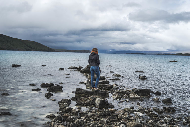 Full length of woman standing on rock amidst lake against cloudy sky