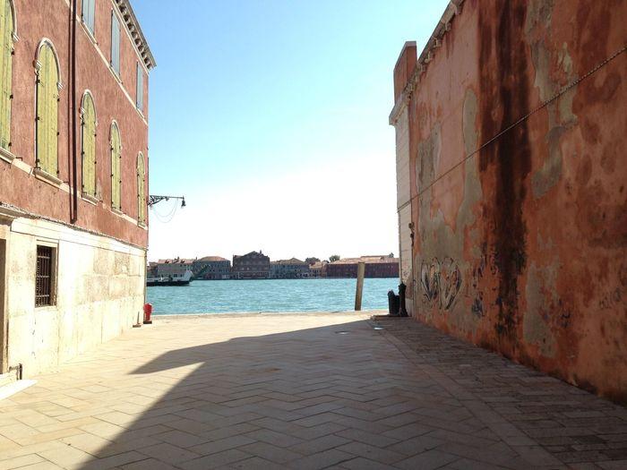 Walkway leading towards giudecca canal against sky