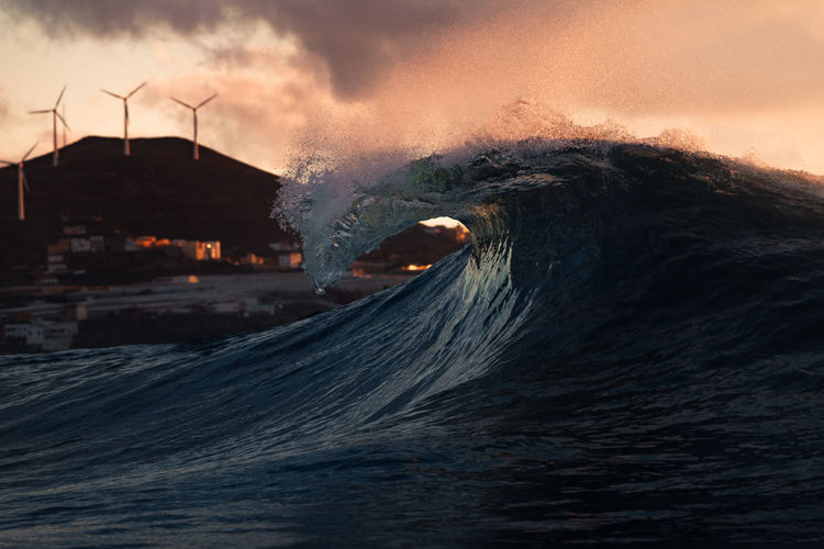 Scenic view of a wave splashing against sky during sunset