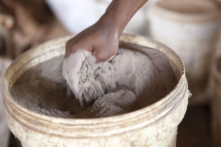 Close-up of hand in clay powder bucket