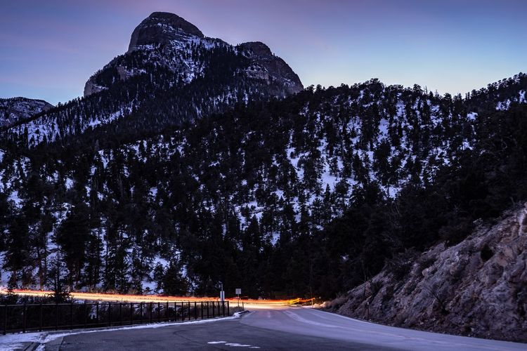 Long Exposure Of Vehicles On Road By Snowcapped Mountains