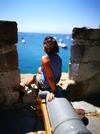 Woman Sitting On Cannon Against Sea At Beach