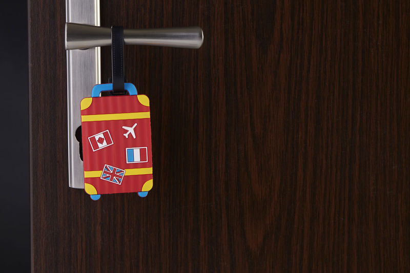 Close-up of luggage label hanging on wooden door