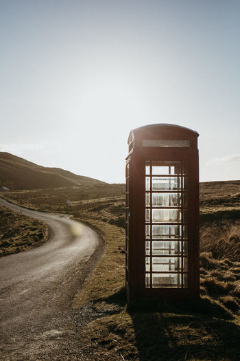 Telephone Booth By Road Against Clear Sky