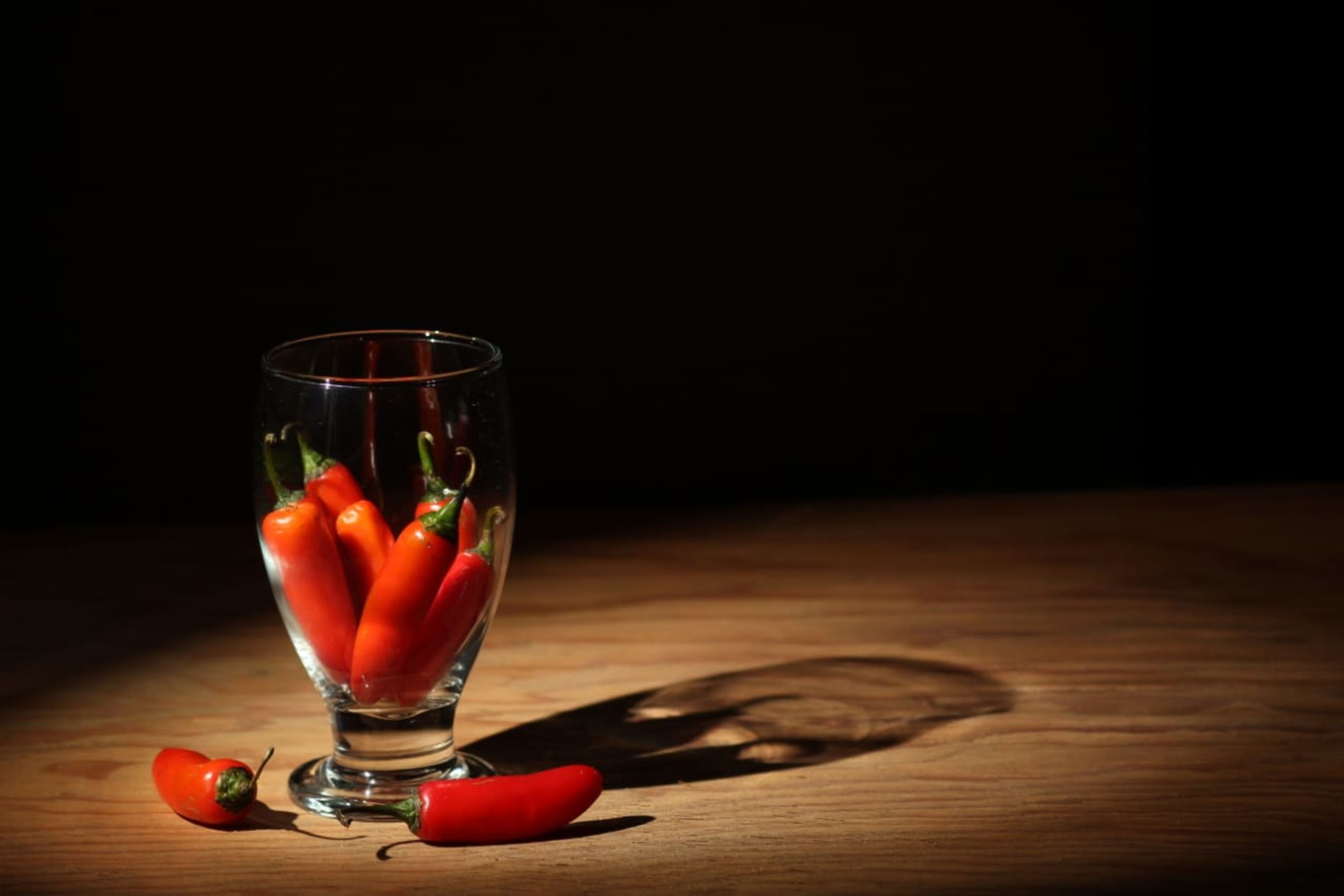 food and drink, red, glass, alcohol, drink, refreshment, alcoholic beverage, drinking glass, household equipment, food, still life photography, wood, indoors, fruit, table, freshness, no people, healthy eating, still life, copy space, cocktail, black background, studio shot, macro photography, wellbeing, wine glass