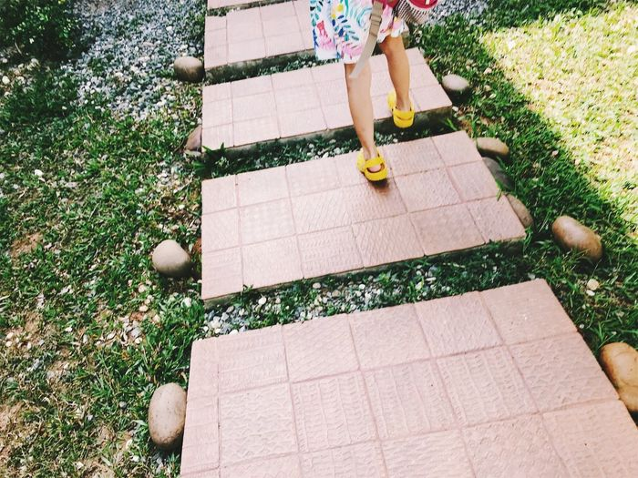 Low section of girl walking on tiles in park