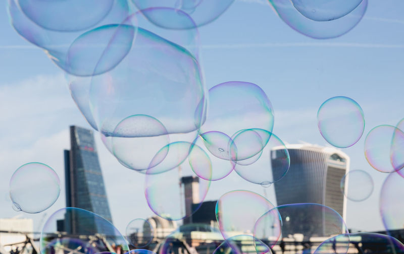 Close-up of buildings seen through bubbles in city against sky