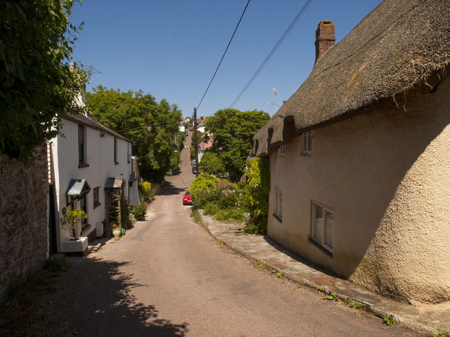 Holcombe Devon England.Holcombe is situated between the seaside resorts of Dawlish and Teignmouth Devon.The village's rich past has been associated with smugglers and been impacted by the growth of the railways - the Bristol to Plymouth main line goes along the coast at Holcombe and is one of the most scenic stretches of the rail network in the country. Smugglers Architecture Blue Building Exterior Built Structure Clear Sky Day Devon Diminishing Perspective Empty Empty Road Footpath Holcombe House Long Narrow No People Outdoors Residential Structure Road Street The Way Forward Tree Village Vivid International