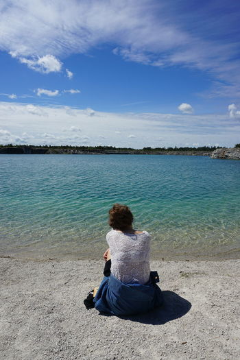 A young woman are sitting on the beach at The Blue Lagoon in Gotland, Sweden Adult Beach Beauty In Nature Blue Casual Clothing Cloud - Sky Day Full Length Gotland Horizon Over Water Leisure Activity Nature One Person Outdoors Real People Relaxation Scenics Sea Sitting Sky Sweden Tranquil Scene Tranquility Tree Water Sommergefühle Breathing Space