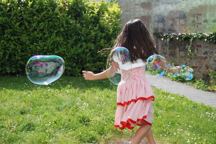 Summer Fun Bubbles Joy Child Enjoying Life Taking Photos Girl EyeEm Gallery Everyday Joy Ladyphotographerofthemonth Youth Joy Of Life Bubble Dress Red Green Striped Rear View Motion Movement Motion Capture Daytime People Childhood