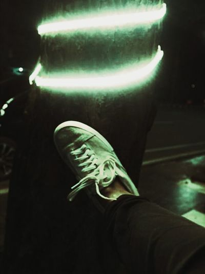 Low section of person wearing illuminated shoes