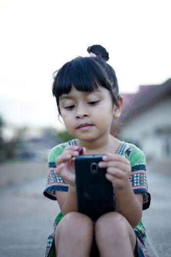 Girl using phone against clear sky