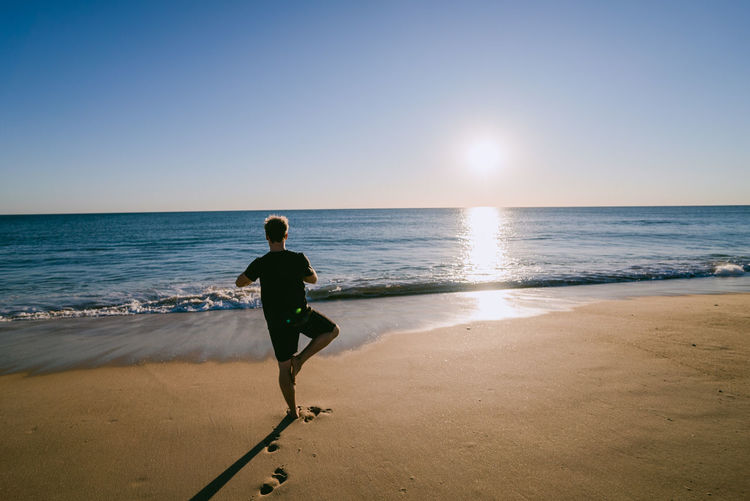 Young man doing yoga on the beach at sunset Portugal Yoga Beach Beauty In Nature Clear Sky Day Fitness Full Length Horizon Over Water Leisure Activity Men Nature One Person Outdoors Real People Sand Scenics Sea Sky Sport Sunlight Vacations Water