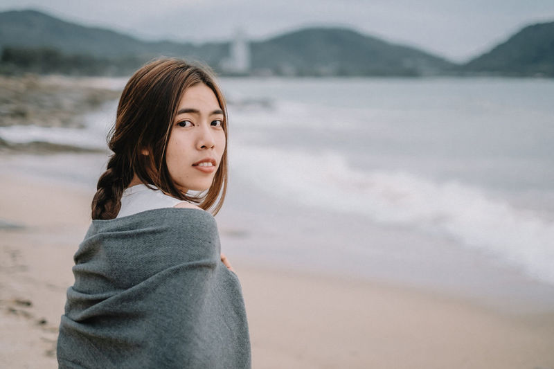 Beach Beautiful Woman Brown Hair Casual Clothing Contemplation Focus On Foreground Hair Hairstyle Hood - Clothing Land Leisure Activity Lifestyles Looking Looking At Camera Mountain Nature One Person Portrait Sea Standing Waist Up Water