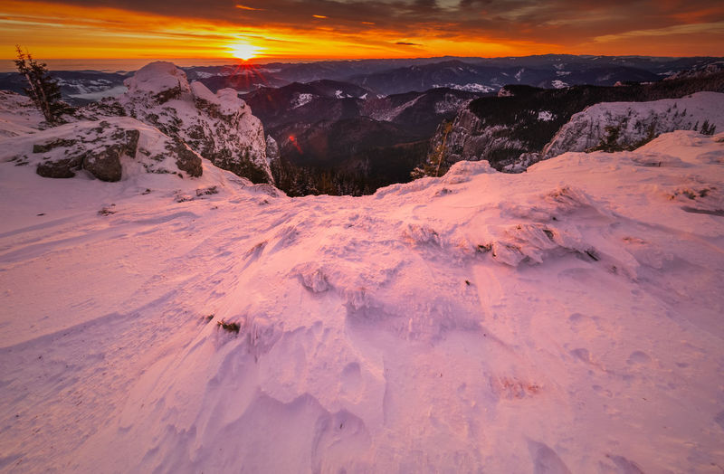 Scenic view of snow covered mountains against sky during sunset in ceahlau mountains
