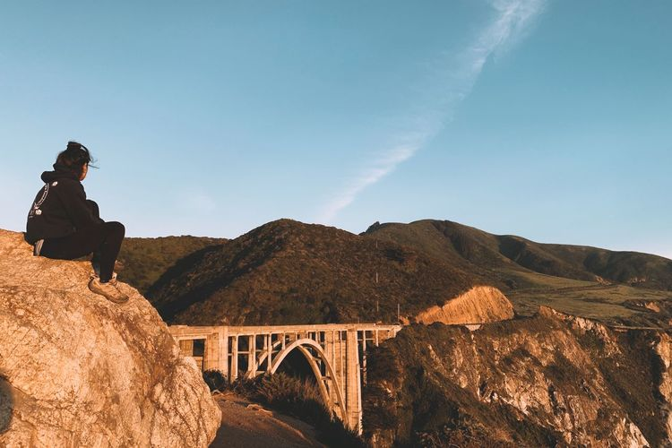 Woman on bridge by mountains against sky