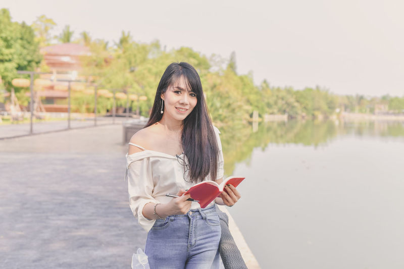Beautiful Woman Beauty Casual Clothing Focus On Foreground Front View Hair Hairstyle Happiness Holding Lake Leisure Activity Looking At Camera Nature One Person Portrait Real People Smiling Standing Teenager Three Quarter Length Water Young Adult Young Women