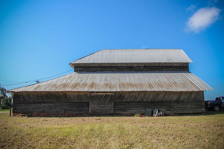 Barn on field against blue sky