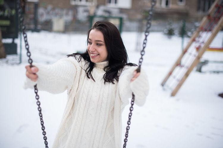 Smiling young woman swinging in snow covered playground